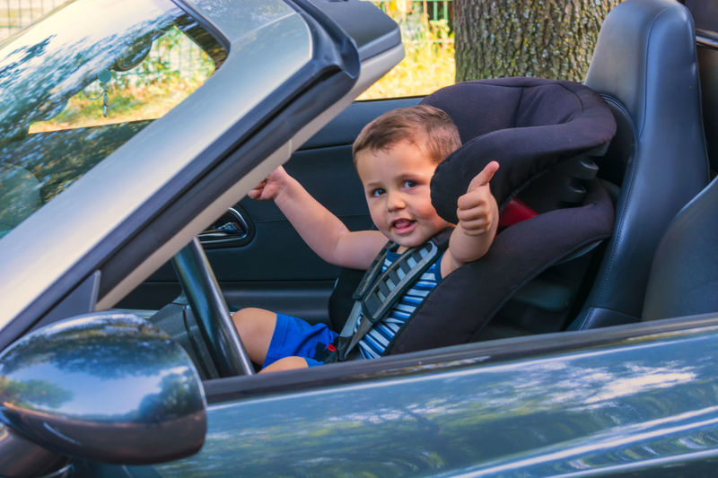 Boy Showing Thumb Up While Sitting In Car
