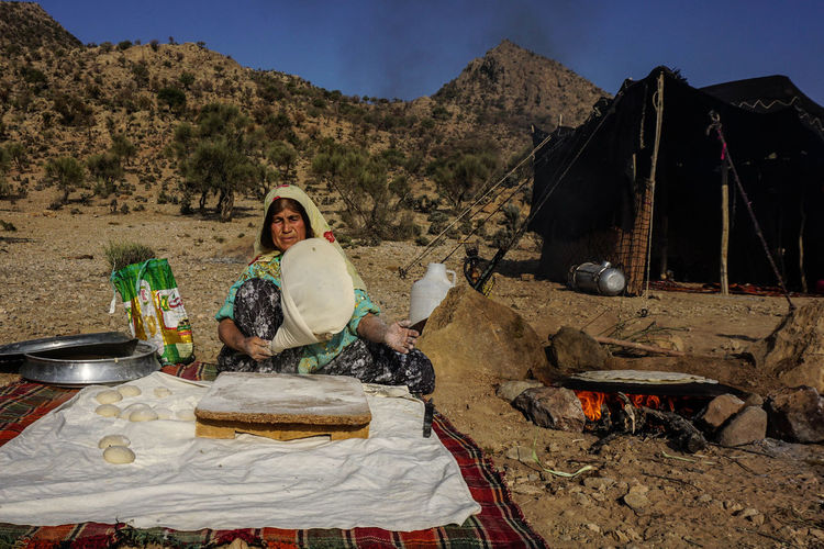 Iran Travel Destinations Travel Photography Nomadic Shia Community Travel Nomadic Life Real People Lifestyles Women Food And Drink Nature Food Leisure Activity Day Portrait Young Adult Adult Looking At Camera Front View Preparation  Container Land Preparing Food Bonfire