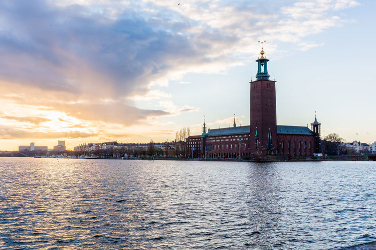 Kungsholmen town hall in city by riddarfjarden during sunset