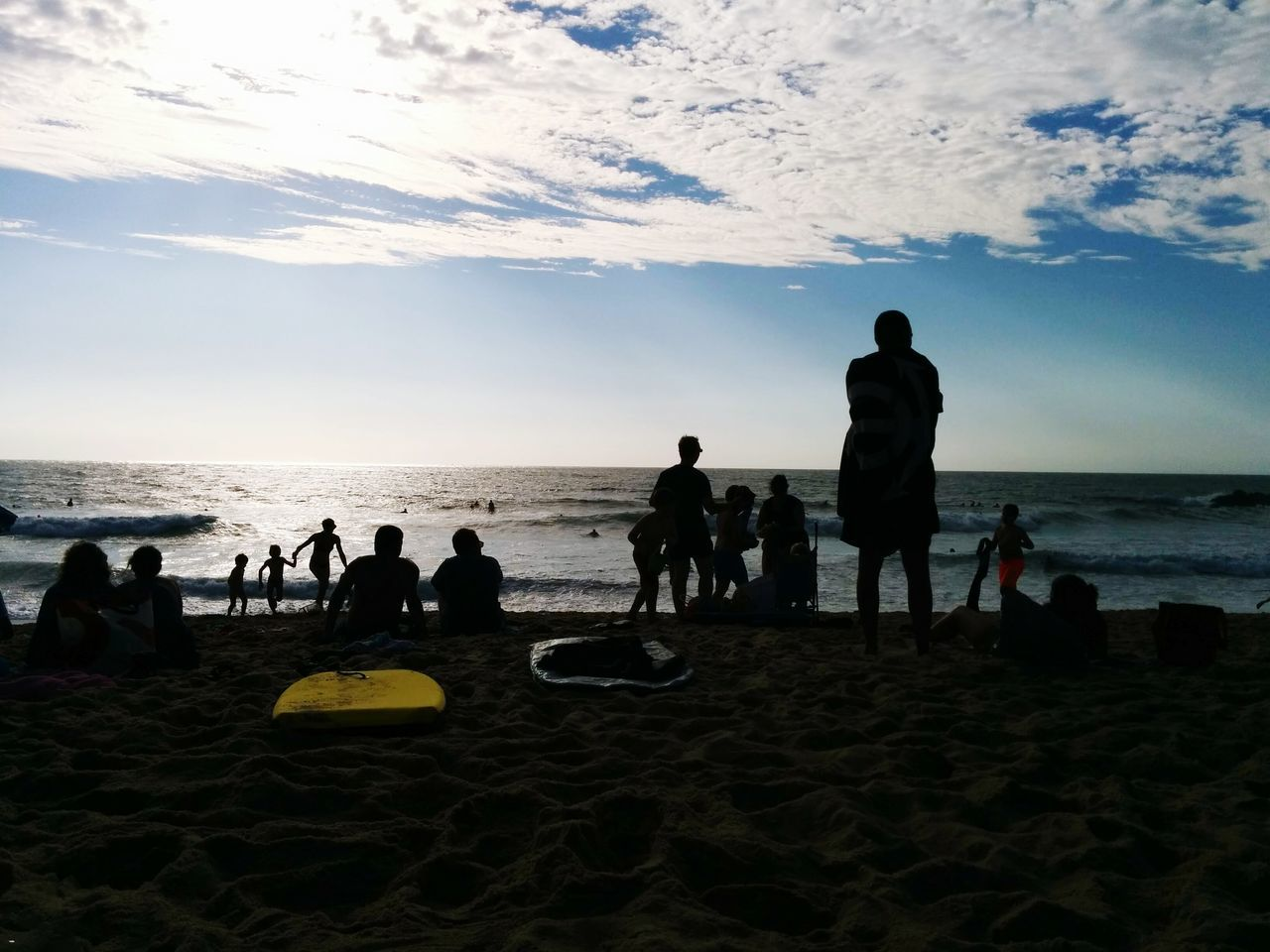beach, sea, sand, horizon over water, water, shore, vacations, sky, leisure activity, nature, real people, silhouette, men, enjoyment, beauty in nature, standing, outdoors, scenics, lifestyles, large group of people, sunset, childhood, day, wave, people