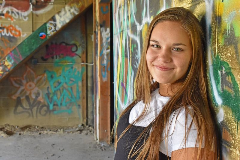 Portrait of a smiling woman standing against graffiti