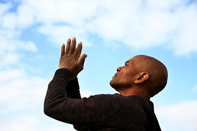 Low angle view of man gesturing against sky