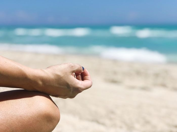 Midsection of man doing yoga at beach on sunny day