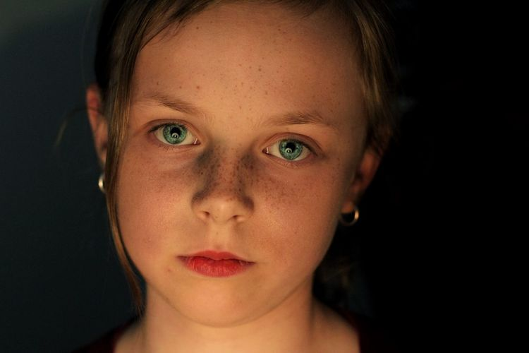 Close-up portrait of girl against black background