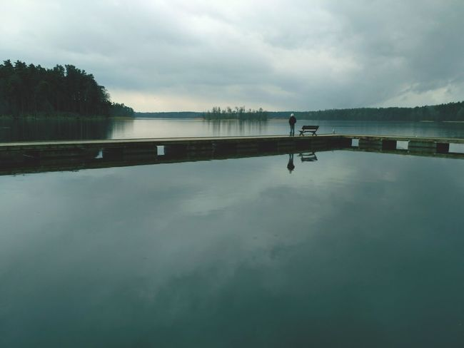 Waiting for the summer. Lone man standing on the bridge by the lake in raining day. Ruciane Nida in Masuria Lakes in Poland. Bridge Man Lake Raining Rainy Alone Waterscape Poland Ruciane Nida Masuria