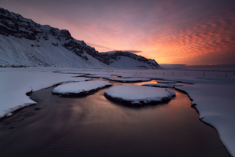 Snow covered shore against sky during sunset