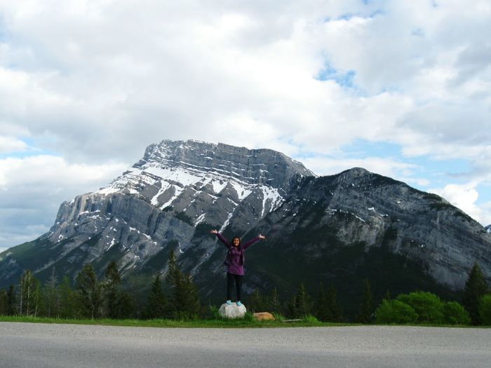 Happy woman with arms raised standing at roadside against snowcapped mountains