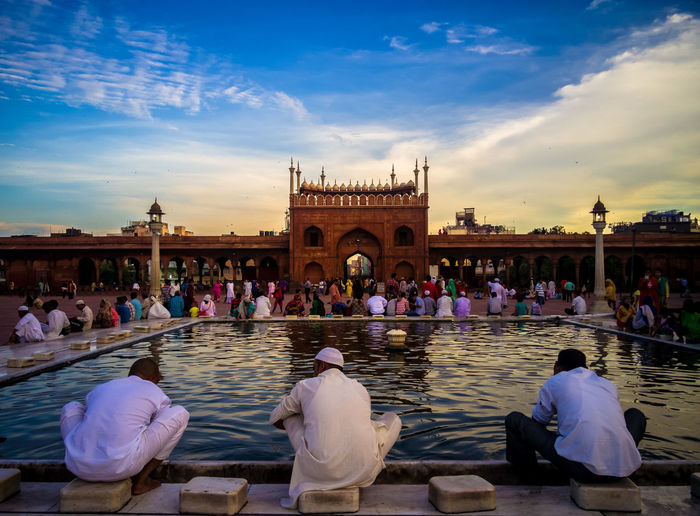 People Resting At Delhi Jama Masjid Mosque Against Sky During Sunset