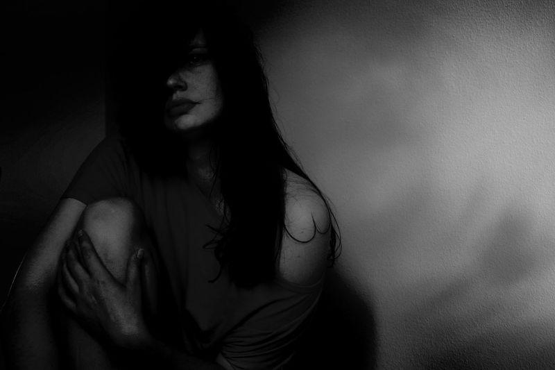 Depressed Woman Sitting In Darkroom