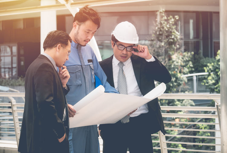 Business people reviewing blueprint outside office