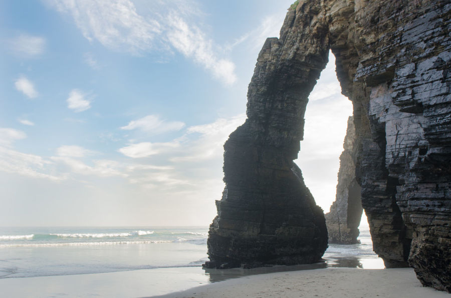 Natural arch at As Catedrais beach - it is the turistic name of Praia de Aguas Santas (Beach of the Holy Waters). Galicia, Spain Arch Beach Beauty In Nature Cantabrian Sea Cathedrals  Coast Day Destination Europe Galicia Lugo Nature Ocean View Outdoors Reflection Reflections In The Water Ribadeo Scenics Sea Sky Spaın Tourism Travel Destinations Water