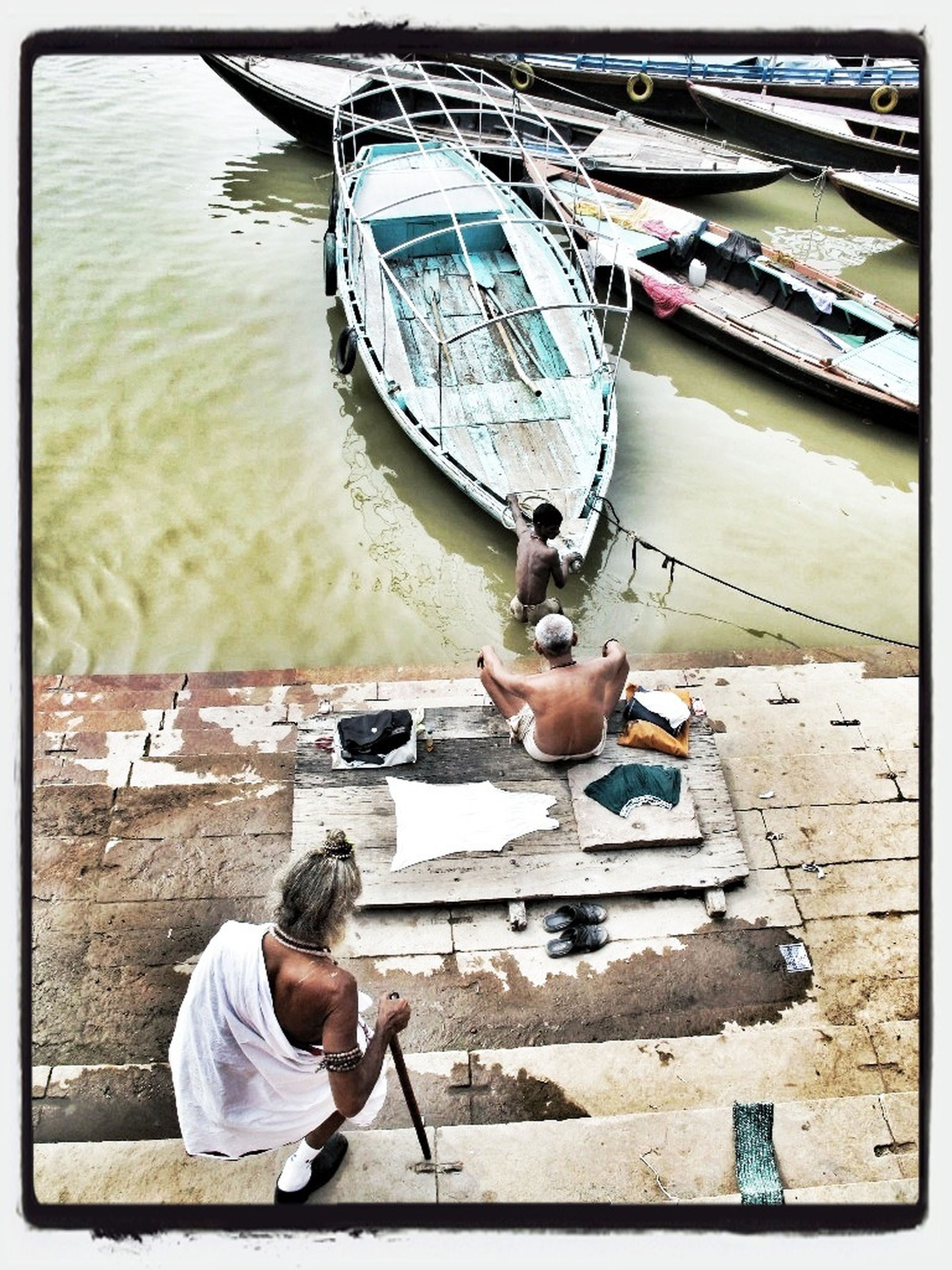 lifestyles, transfer print, leisure activity, auto post production filter, full length, water, holding, casual clothing, childhood, person, nautical vessel, boys, men, sitting, transportation, mode of transport, high angle view, side view