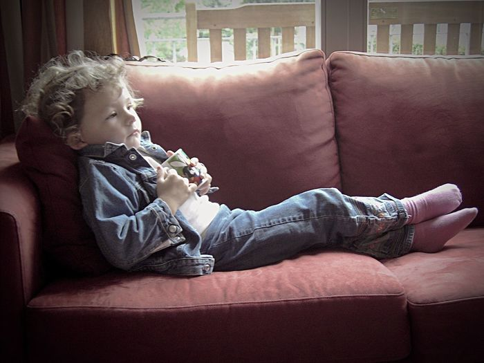 Side view of boy holding cup while relaxing on sofa at home