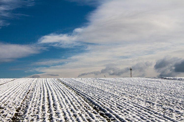 High angle view of snow covered on agricultural field against cloudy sky