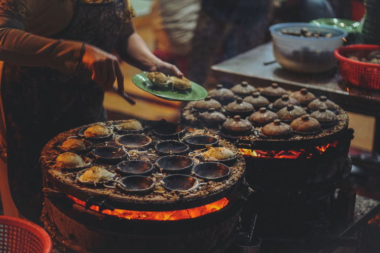 Midsection of female vendor cooking food at night
