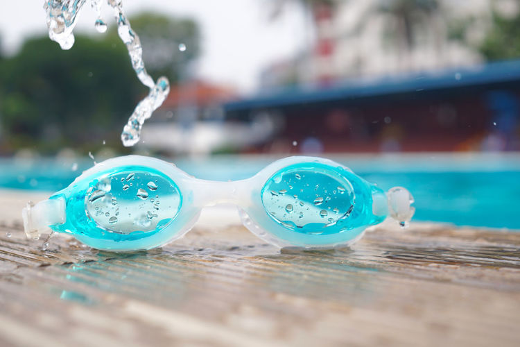 Close-up of wet swimming goggles at swimming pool
