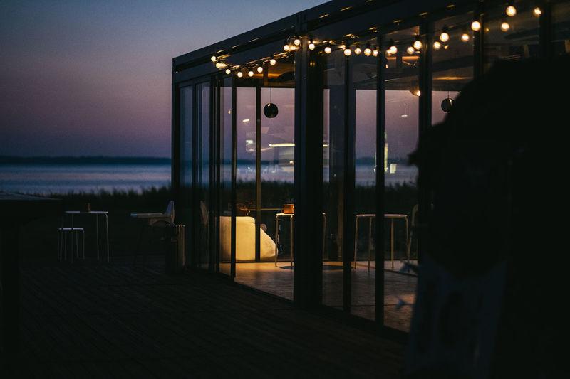 Silhouette man on illuminated beach against sky at night