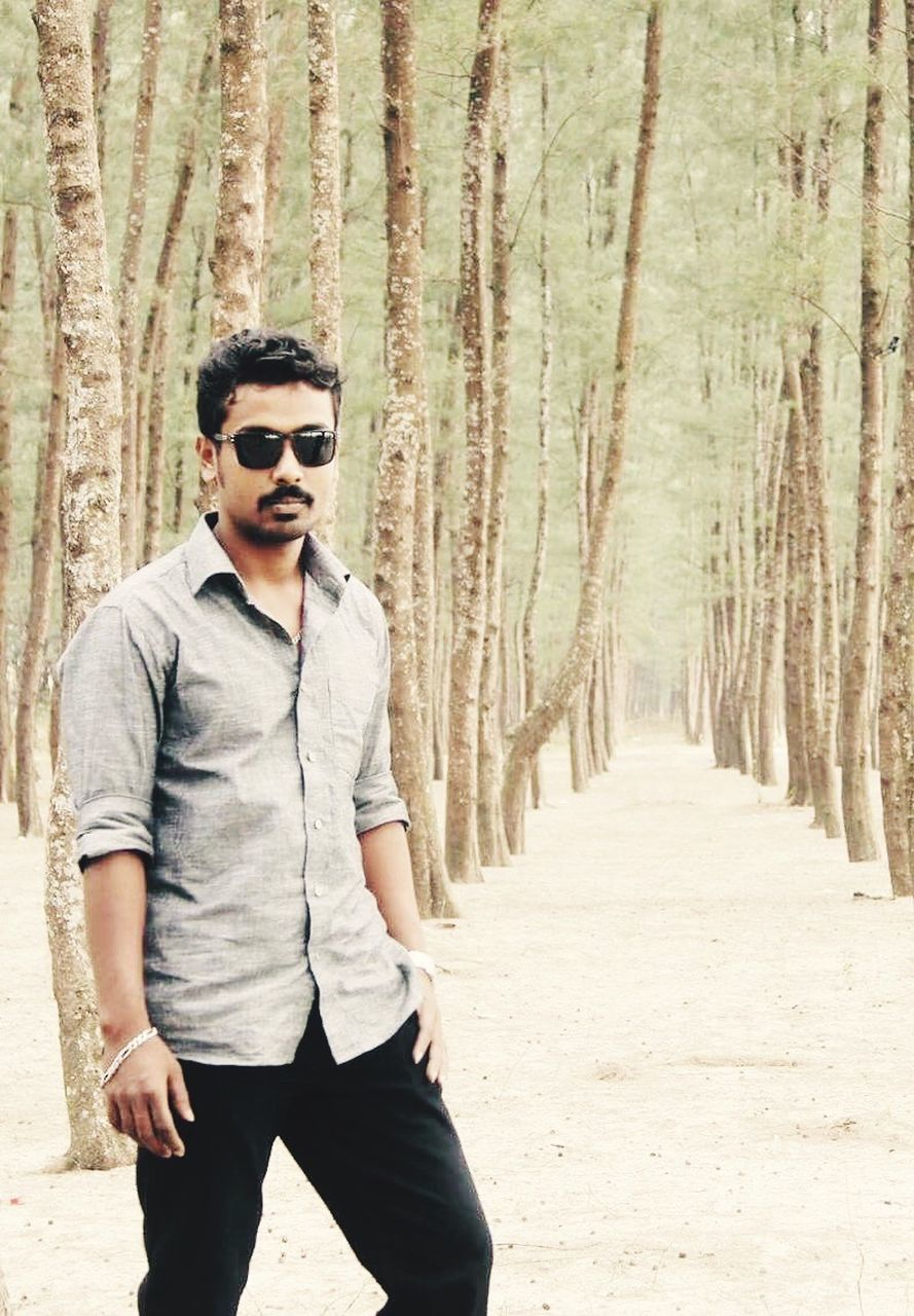 sunglasses, young adult, front view, young men, tree, one person, tree trunk, portrait, forest, outdoors, day, standing, lifestyles, real people, nature, adult, adults only, people