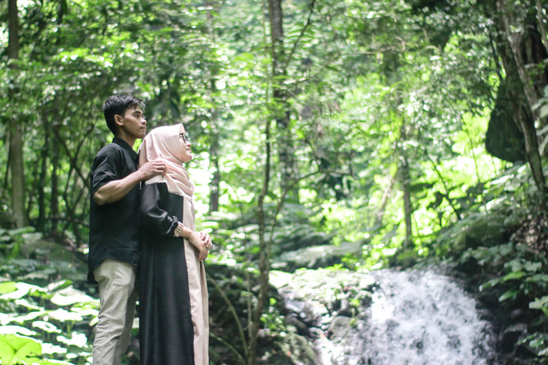 Couple standing by waterfall in forest