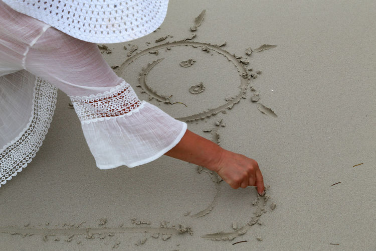High angle view of woman drawing sun on sand at beach