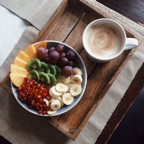 High angle view of coffee and fruits on table
