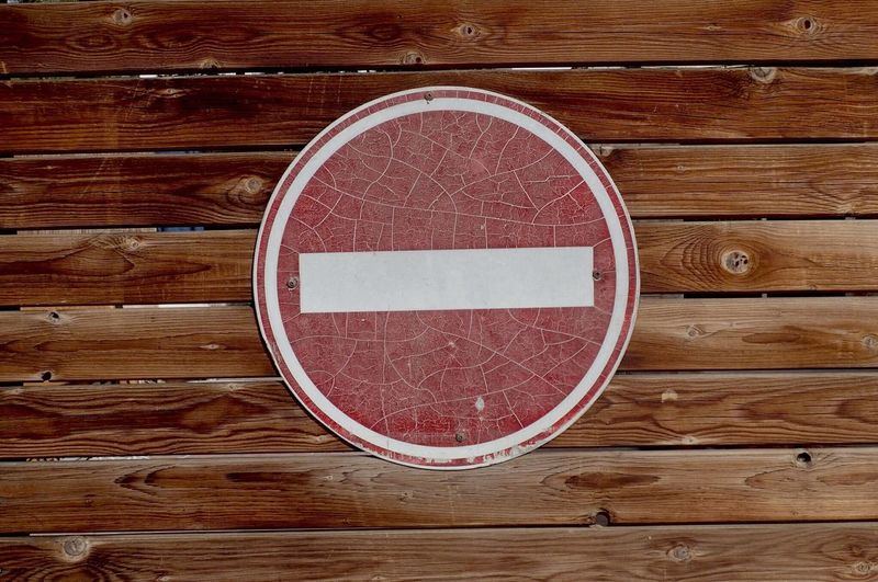 Close-up of old stop sign on wooden wall