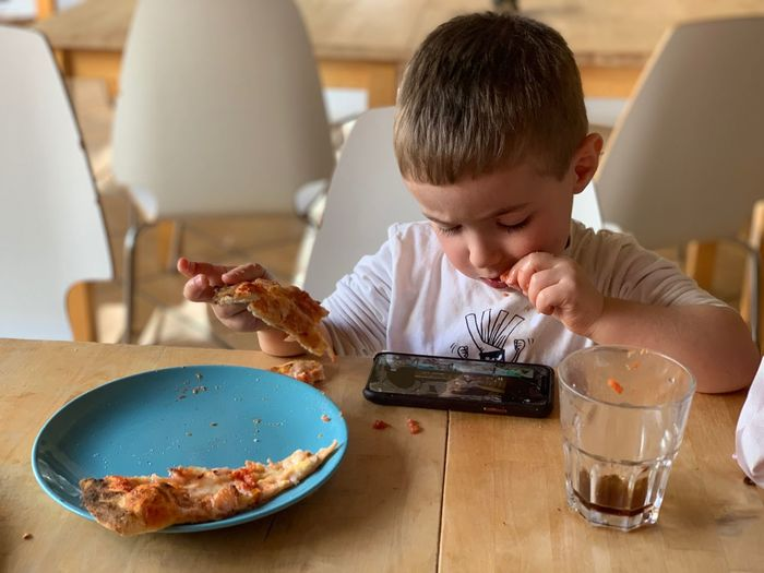 Lunch Pizza Food And Drink Food Lifestyles One Person Table Childhood Real People Child Headshot Indoors  Boys Wireless Technology Meal Males  Men Breakfast Eating Utensil Sitting Kitchen Utensil