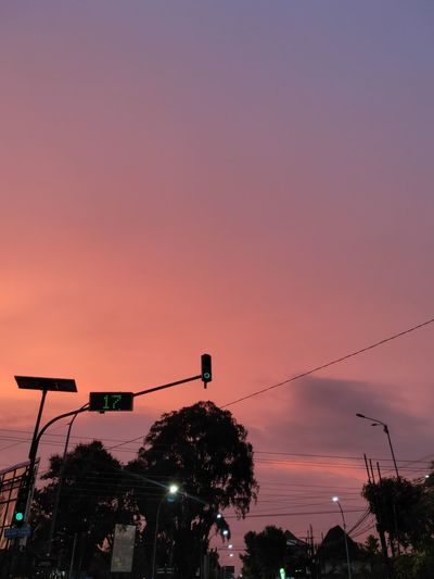 Low angle view of illuminated street lights against sky at sunset