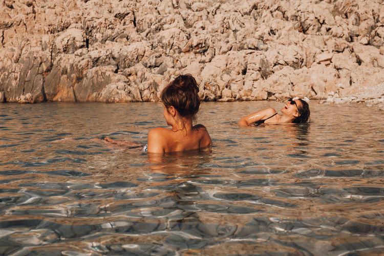 Rear view of two women on rock
