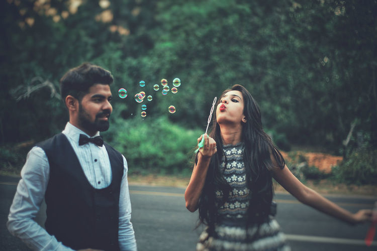 Boyfriend looking at girlfriend blowing bubbles on road