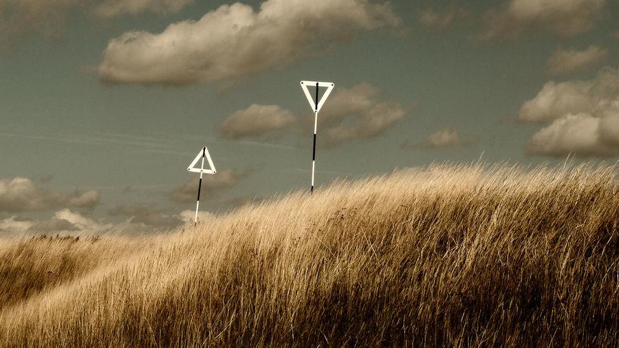 Wind turbines on field against sky
