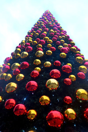 Christmas Decorations christmas tree Christmas Tree Ball Low Angle View Sky Decoration Multi Colored Celebration No People Christmas Christmas Ornament Christmas Decoration Illuminated Nature Outdoors Holiday Tree Day Religion Holiday - Event Built Structure
