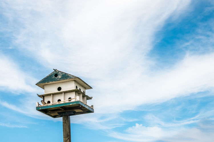 Low angle view of  large birdhouse in need of repair, a bird perched set against a whispy sky.
