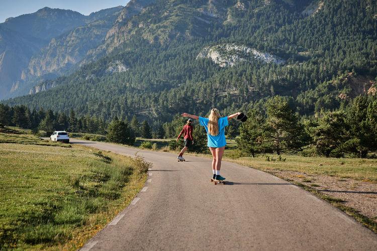 Rear view of men walking on road by mountain