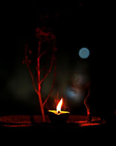 Close-up of lit diya burning at night