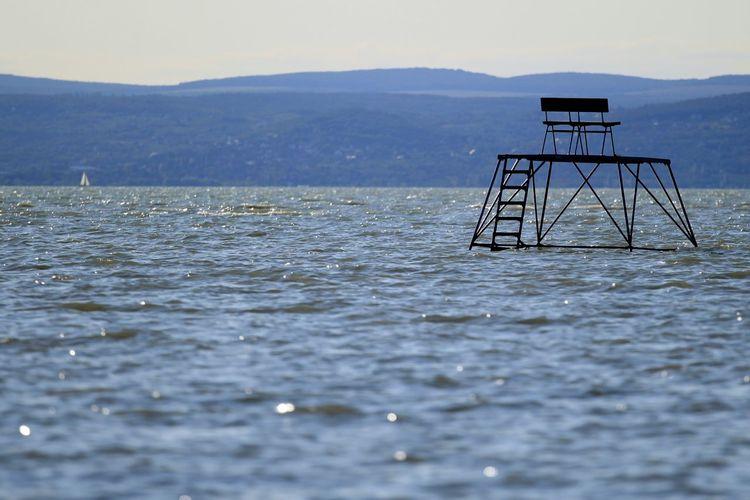 Lifeguard chair amidst river against mountain