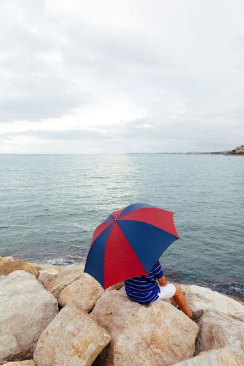Umbrella on rock by sea against sky