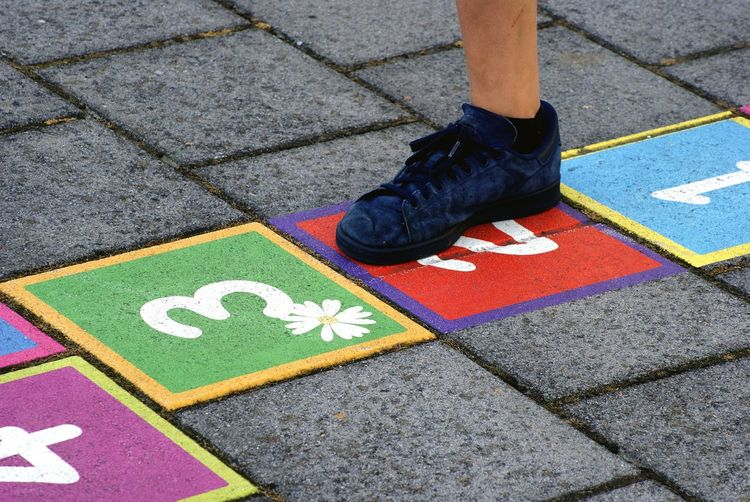 Low section of child playing hopscotch on footpath