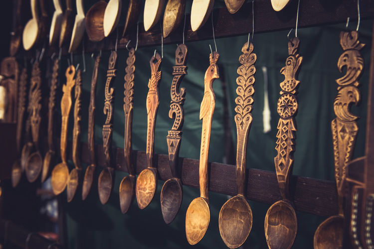 Vintage ornamental wooden spoons hanging in a fair Cooking Ornamental Romania Utensils Used For Food Arrangement Carved Wood Fair Flatware Food For Sale For Sale Items Handicraft Handmade Hanging In A Row Kitchenware Marketplace Old Spoons Utensils Utensils Kicthen Variation Vintage Wooden Woodworking