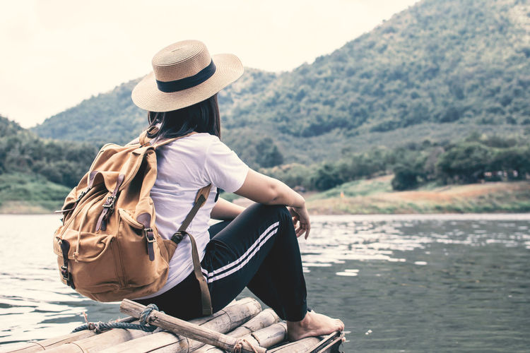 Rear view of woman sitting by lake on wooden raft