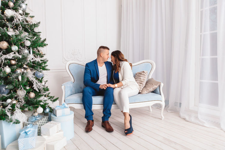 Couple sitting on sofa by christmas tree at home