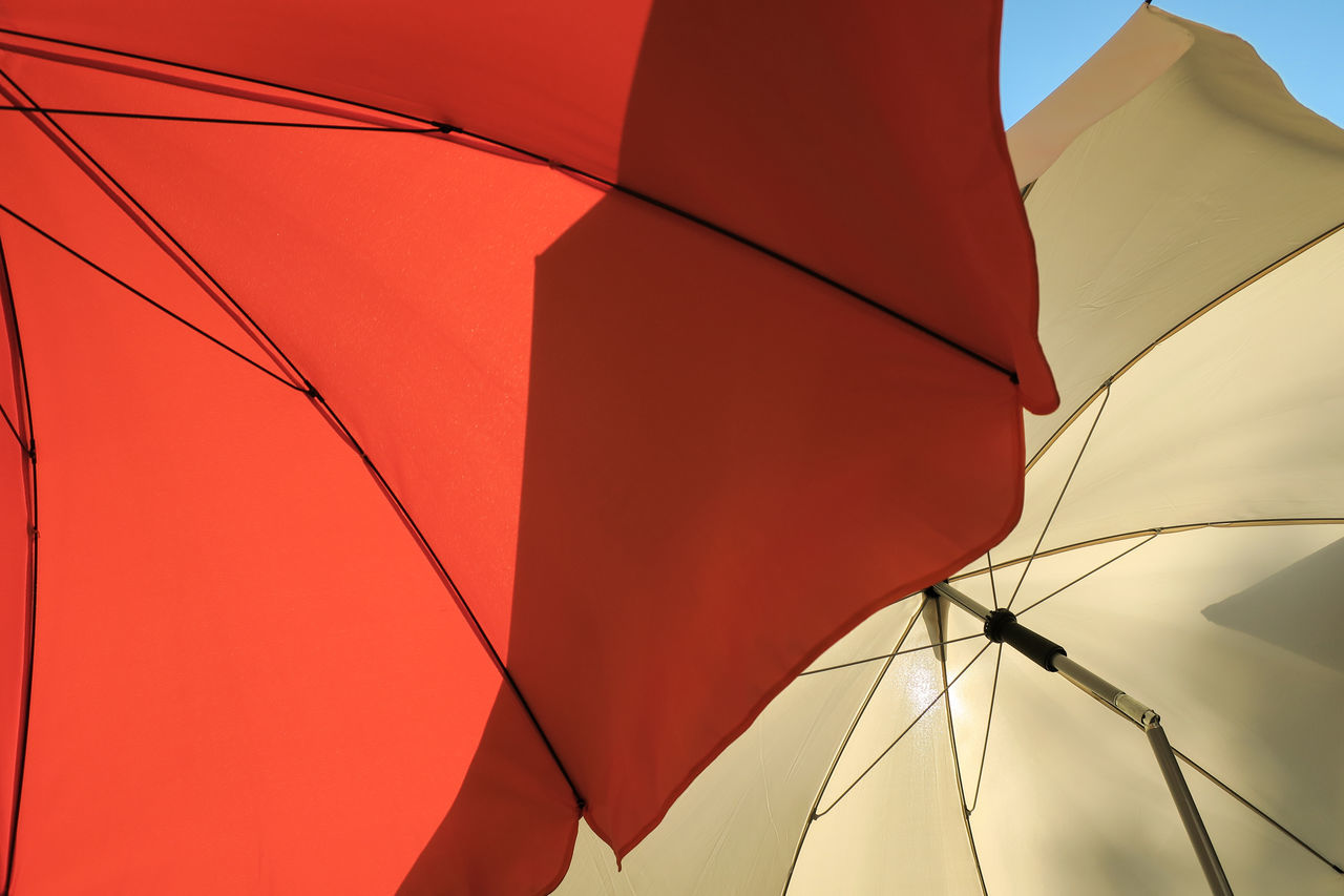 Low Angle View Of Red And Beige Parasols