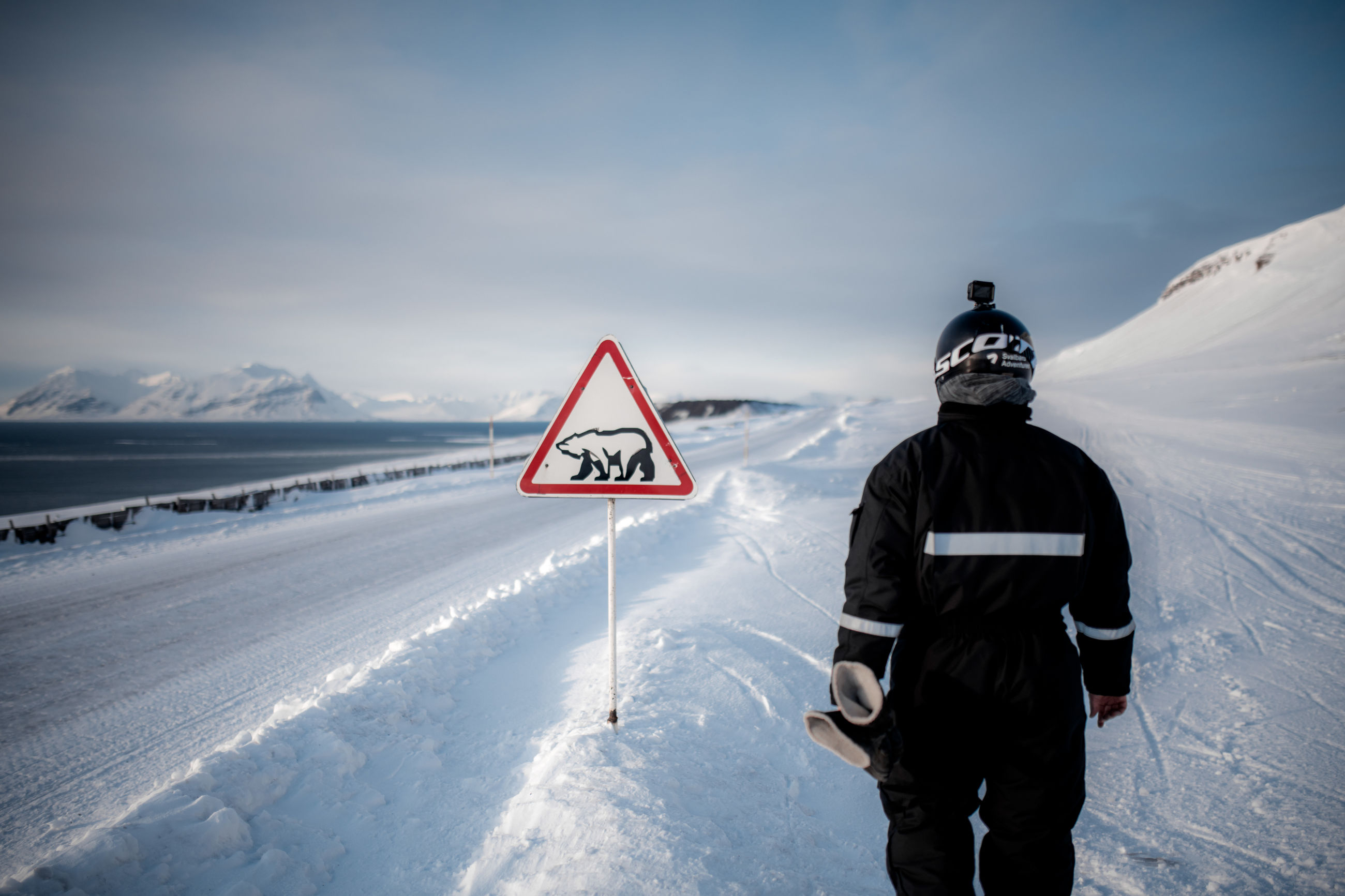 snow, winter, cold temperature, mountain, communication, sign, rear view, nature, sky, scenics - nature, beauty in nature, real people, non-urban scene, day, clothing, warm clothing, leisure activity, one person, warning sign, mountain range, guidance, outdoors, snowcapped mountain