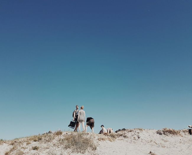 People on sand against clear blue sky