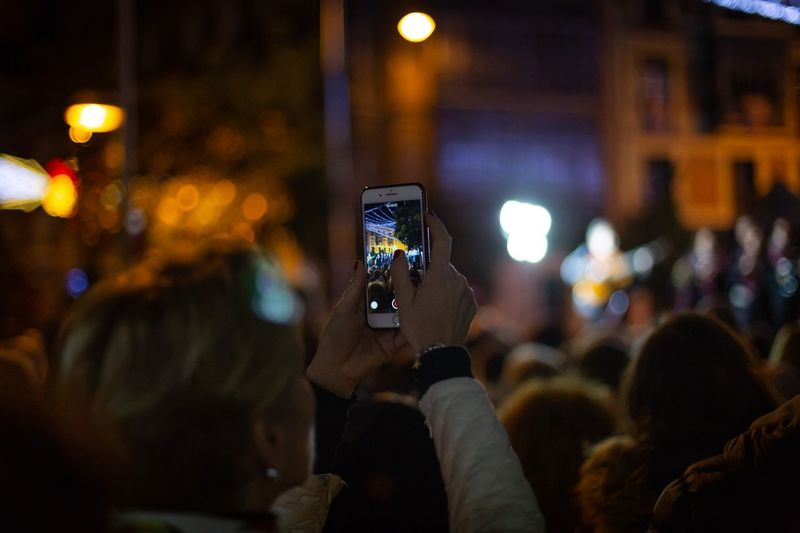 Close-up of woman filming with mobile phone in city at night
