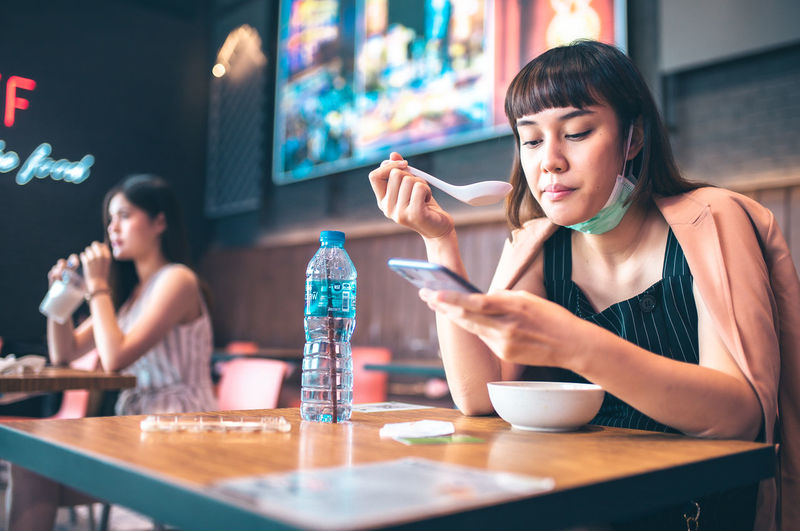 Young woman using phone while sitting on table at cafe