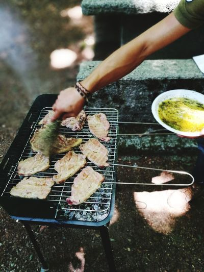 High angle view of woman preparing food on barbecue grill