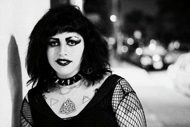 Portrait of punk woman standing by wall at night