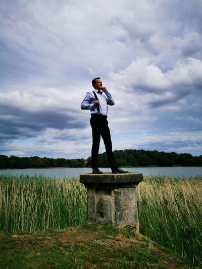 Low angle view of man standing on built structure against sky