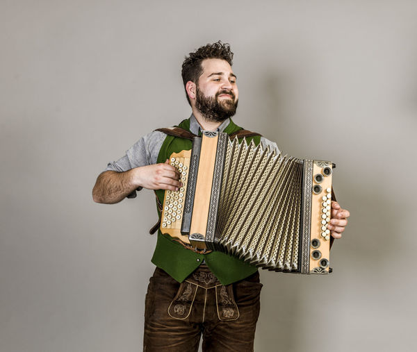 Musician Costume Leather Trousers Tradition Traditional Austria Green Pose Accordion Man Young Shorts Friendly Proud Happy Play Music Fun Joy Single One Background Copy Space Studio Entertainment Mountains Shirt STAND Hobby Leisure Cool Studio Shot One Person Three Quarter Length Indoors  Front View Standing Young Adult Gray Young Men Gray Background Holding Casual Clothing Looking Away Looking White Background Men Beard
